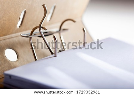 Selective focus on an opened archive ring binder with a blank paper Royalty-Free Stock Photo #1729032961