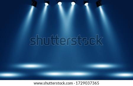 Spotlights illuminate empty stage blue background. Royalty-Free Stock Photo #1729037365
