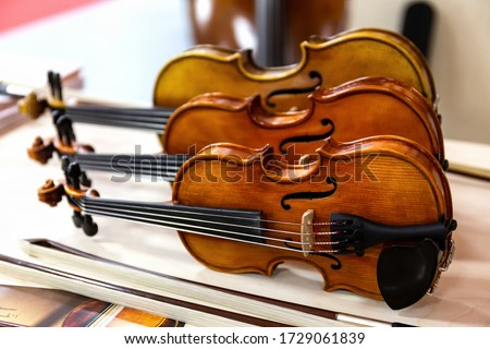 Three classical violins standing on a table. Stringed musical instruments of a Symphony orchestra. Royalty-Free Stock Photo #1729061839
