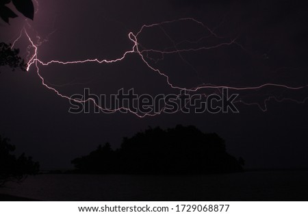 Island silhouette and lightning during night storm. Almost black night picture with electrifying thunderstorm lights