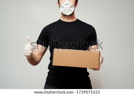 Delivery man wearing a protective mask and medical gloves holds the box and gives a thumbs up against an isolated white background #1729071622
