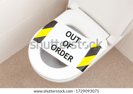 Household toilet with a sign that reads 'out of order'