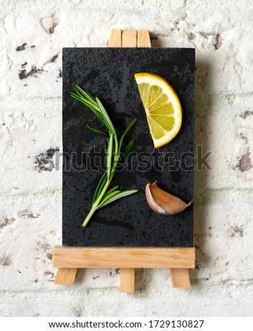 A sprig of rosemary, a slice of lemon and a clove of garlic on a slate Board on a white brick background. Concept of a picture, postcard or calendar