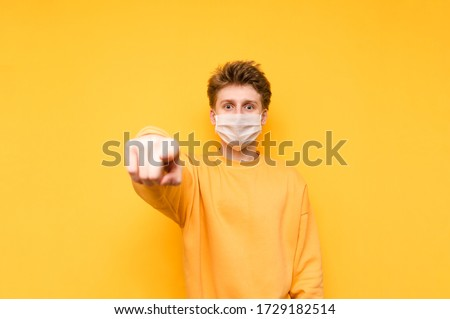 Emotional guy in a gauze mask shows his finger to the camera and looks with a shocked face, isolated on a yellow background. Coronavirus pandemic. COVID-19. Quarantine. #1729182514