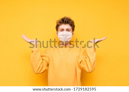 Confused guy in bright casual clothes and a white gauze mask looks at the camera and spreads his arms to the sides on a yellow background. Coronavirus pandemic. COVID-19. Quarantine. #1729182595