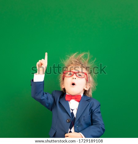 Bright idea! Funny child student in class. Happy kid against green chalkboard. Online education and e-learning concept. Back to school #1729189108