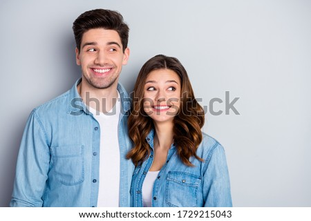 Photo two funny beautiful people lady guy stand side by side look tricky side empty space chatterbox childish mood wear casual denim shirts outfit clothes isolated grey color background