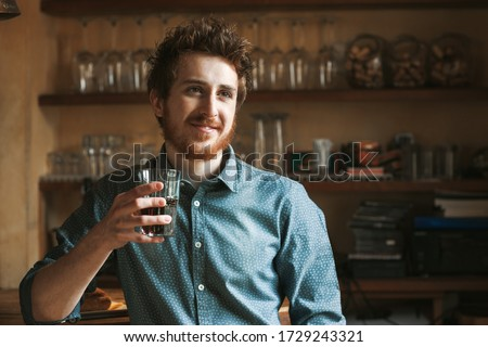 Hipster young man smiling and drinking a glass of coke with bar wooden shelves on background #1729243321