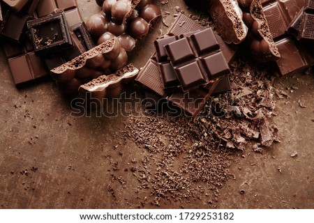 Composition of bars and pieces of different milk and dark chocolate, grated cocoa on a brown background top view close up #1729253182