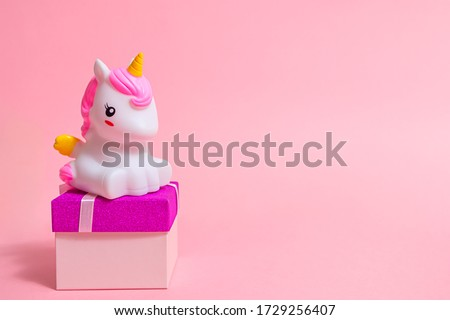 A cute cartoon unicorn figurine stands on a gift box on a pink background. Gifts for the girl on a holiday: birthday, Christmas, International Women's Day, Valentine's Day