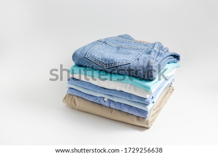 Stack of colorful perfectly folded clothing items. Pile of different pastel color shirts, sweaters isolated and other garments on white background. Close up, top view, copy space. Royalty-Free Stock Photo #1729256638