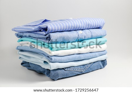 Stack of colorful perfectly folded clothing items. Pile of different pastel color shirts, sweaters isolated and other garments on white background. Close up, copy space. Royalty-Free Stock Photo #1729256647
