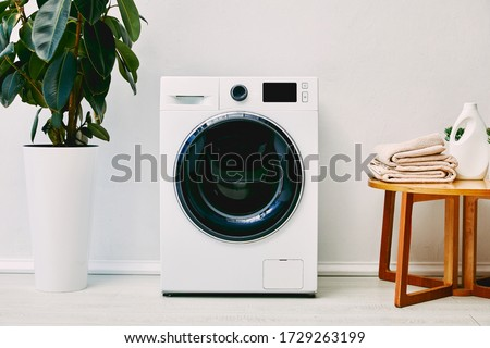 green plant near washing machine, wooden coffee table with towels and detergent bottle in bathroom #1729263199