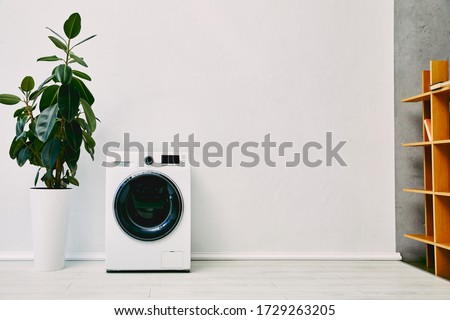 green plant near modern washing machine and wooden rack in bathroom #1729263205