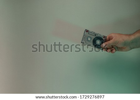 Hand holding audio cassette tape in the color light. Beautiful minimal in neon light. Minimalism retro style concept. Background pattern for design.