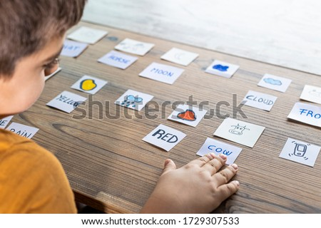 Little kid playing with cards of words and pictures. Time to learn. Education concept.
