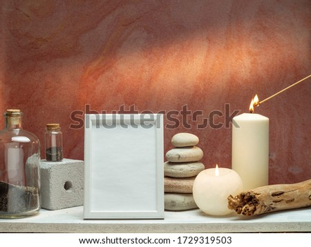 Room decoration with candles, rocks, bottle with black sand and picture frame mockup on white shelf against old brick color wall.
