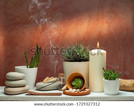 Room decoration with scented incense stick, candle, rocks and cactus on white shelf against old brick color wall.