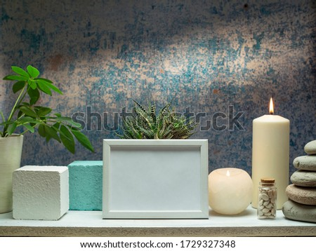 Picture frame mockup and plants with candles on white shelf against old blue wall.