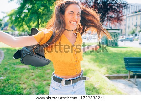 young woman outdoor having fun laughing spreading arms - getting away from it all, spontaneous, positive emotions concept Royalty-Free Stock Photo #1729338241