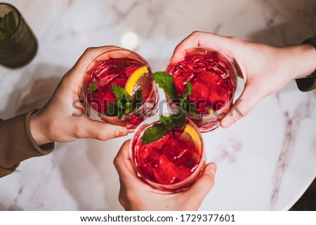Friends toasting with sangria in a Spanish restaurant. Cheers! #1729377601