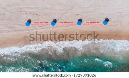 Aerial View on Public Beach coastline, ocean waves and arrow with social distance sign 6 feet between beach umbrellas. Beach reopening social distancing during coronavirus pandemic.