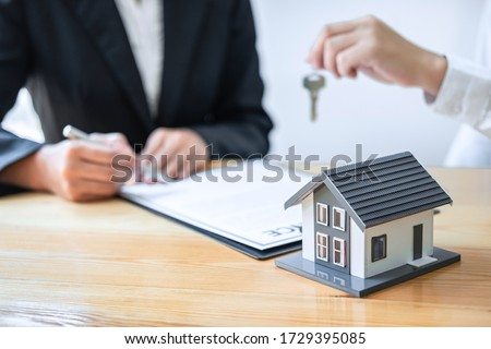 Home Insurance and Real estate investment concept, Sale agent giving house key to new client after signing agreement contract with approved property application form. #1729395085