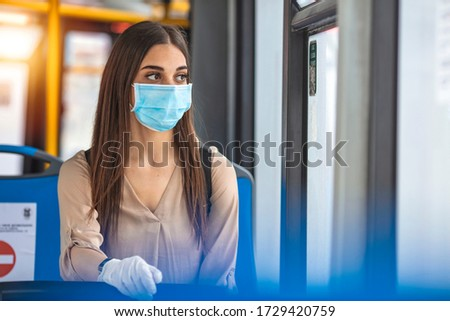 Woman wearing a sterile protective medical mask against coronavirus, Covid-2019 Asian pandemic sars virus while going in a public bus in a European city street looking ahead. #1729420759