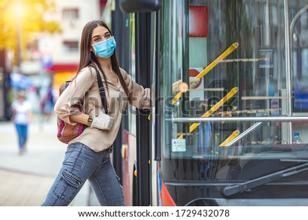 Young female boarding a city bus. Virus pandemic and pollution concept. Woman getting on the bus with protective medical mask and gloves against coronavirus, Covid-2019  #1729432078