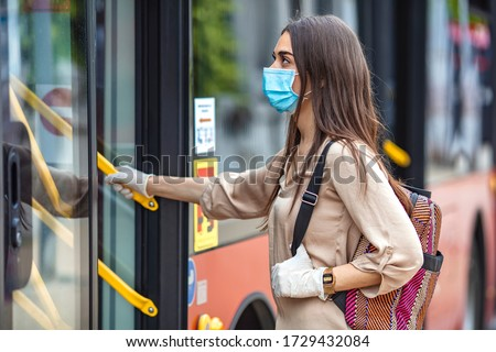 Young female boarding a city bus. Virus pandemic and pollution concept. Woman getting on the bus with protective medical mask and gloves against coronavirus, Covid-2019  #1729432084