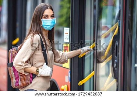 Virus pandemic and pollution concept. Woman getting on the bus. Virus protection in public transportation. Woman wearing surgical protective mask going to work #1729432087