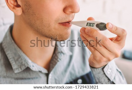 Closeup ill hipster man freelancer holding digital thermometer in mouth for measuring body temperature at home. Sick businessman student check temperature with electronic thermometer. Health care #1729433821