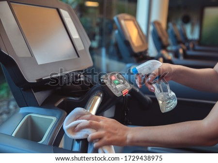 Gym cleaning and disinfection. Infection prevention and control of epidemic. Staff using wipe and alcohol sanitizer spray to clean treadmill in gym. #1729438975