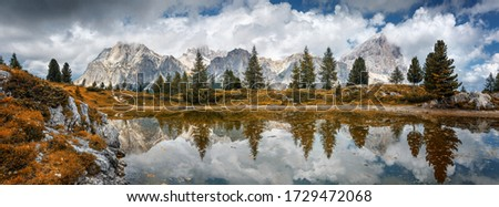 Fantastic nature landscape. Fairy tale alpine lake with majestic rocky peak  on background. Amazing Autumn Scenery with calm lake and reflection. Picture of wild area. Limides lake in summer season