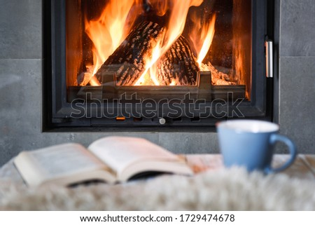 Open book, cup of tea and warm plaid near burning fireplace. Hygge concept Royalty-Free Stock Photo #1729474678