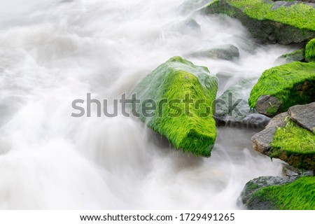 lens painting, Photo taken in the camera's slow shutter speed to make this view look nice when you see the green moss on the rocks after in the sea .