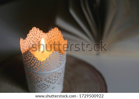 Lit candle and open book on a table. Dark and cosy atmosphere. Selective focus. #1729500922