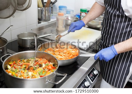 Man in apron and gloves cooking fresh vegetables for healthy food take away delivery, quarantine #1729510300