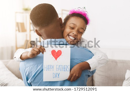 Father's day. Pretty afro girl giving dad postcard and hugging him, free space #1729512091
