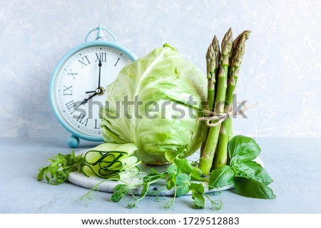 Alarm clock, Asparagus, microgreens, cucumber and cabbage - fresh green vegetables. Ketogenic diet, intermittent fasting, weight loss Royalty-Free Stock Photo #1729512883