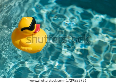 Yellow rubber duck floating on blue water in a pool on a hot summer day, taking a bath and swimming Royalty-Free Stock Photo #1729553986