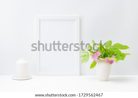 Home interior with decor elements. Mockup with a white frame and small flowers and green leaves in a vase on a light background #1729562467