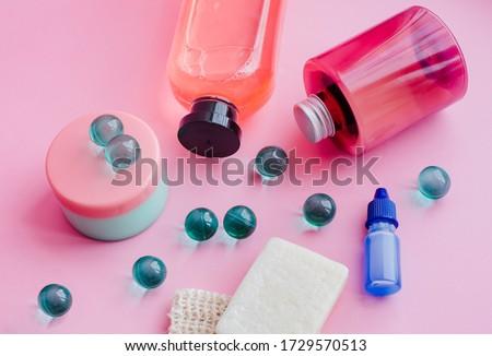 A set of toiletries, jars of body cosmetics. Deodorant, shampoo, spray, cream, scrub, bath balls on a pink background. Personal care concept. #1729570513