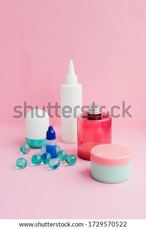 A set of toiletries, jars of body cosmetics. Deodorant, shampoo, spray, cream, scrub, bath balls on a pink background. Personal care concept. #1729570522