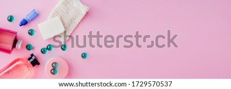 A set of toiletries, jars of body cosmetics. Deodorant, shampoo, spray, cream, scrub, bath balls on a pink background. Personal care concept. #1729570537