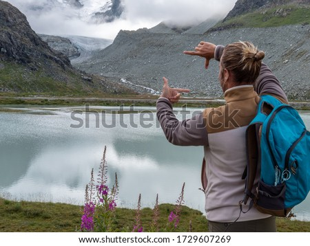 Hiker on mountain trail framing nature with hands, glacier area. People summer activity. Man picture framing landscape with hands