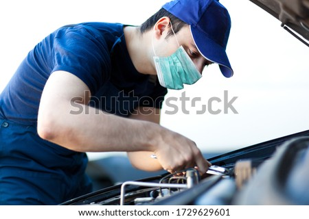 Mechanic fixing a car engine wearing a mask, coronavirus concept #1729629601