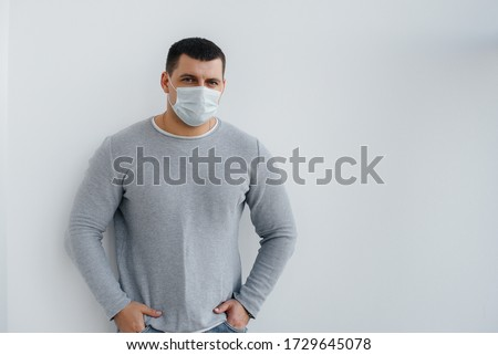 A young man stands on a gray background wearing a mask during a quarantine with free space. Quarantine in the mask #1729645078