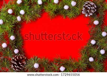 coniferous branches decorated with white round cotton, imitation of snow, red background for the new year
