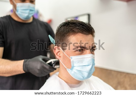 Man Getting Hair Cut at the Barbershop Wearing Mask. Professional Barber Wearing Gloves. Young Man Getting Hair Cut on Coronavirus Pandemic. Covid-19 Concept. #1729662223